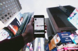 Сотовый телефон в руке на фоне небоскребов