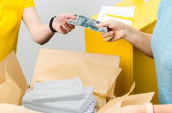 Тысяча рублей передается одним человеком в руку другого на фоне коробок