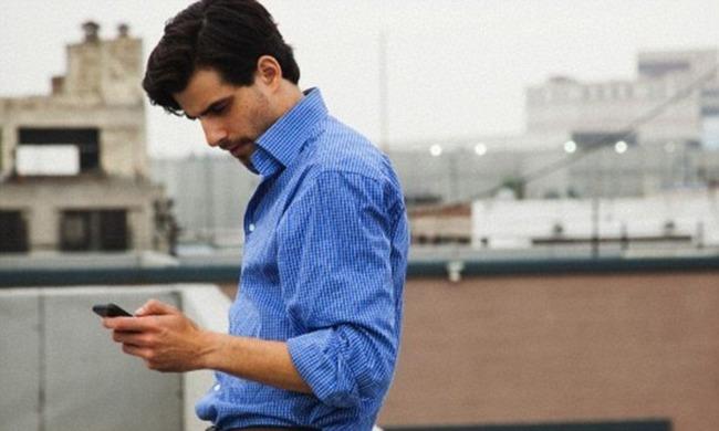 Мужчина стоит на крыше со смартфоном